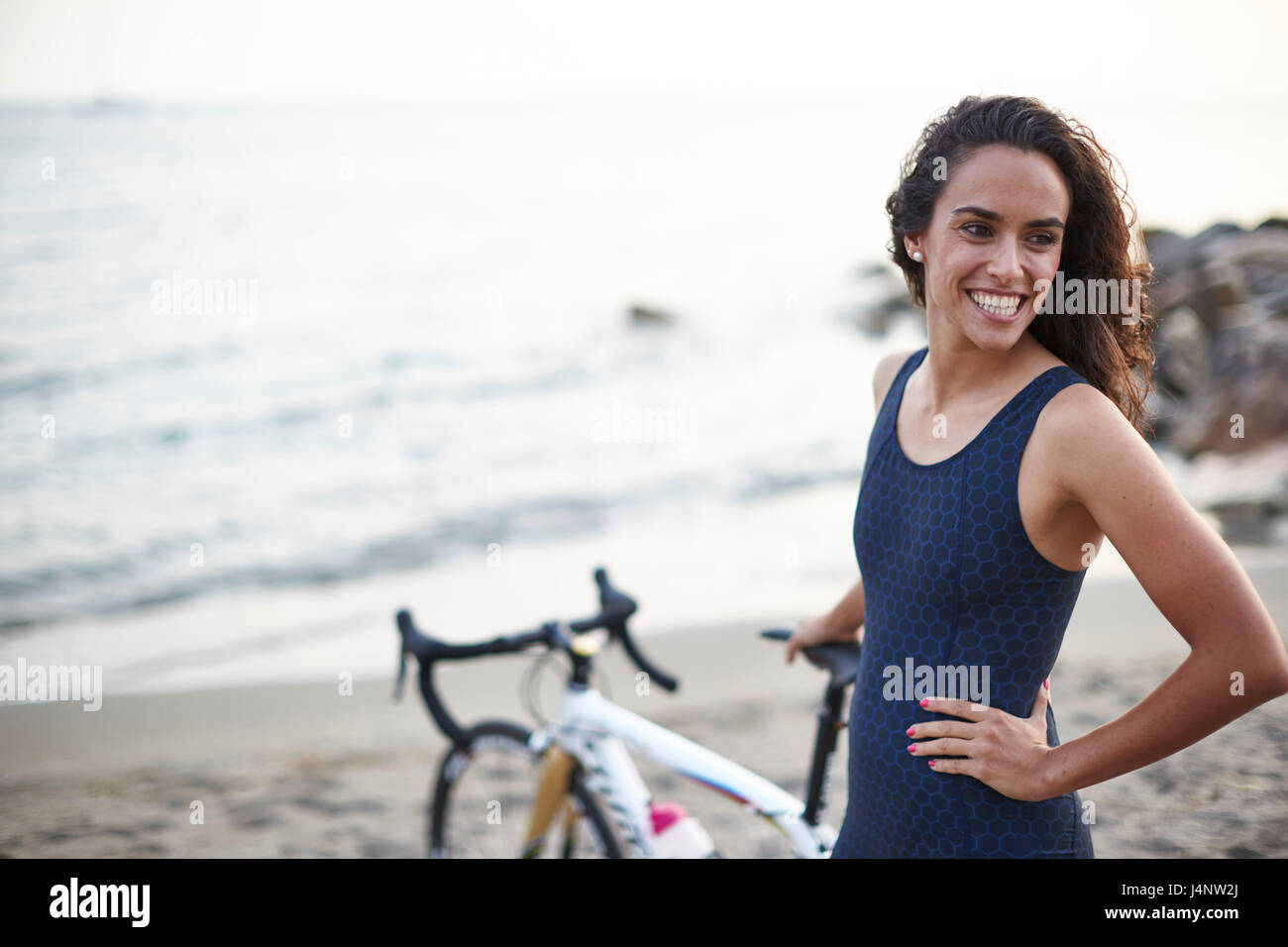 A female triathlete on the beach wearing her triathlon suit - Stock Image