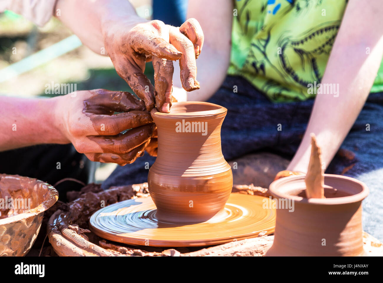 Potter's hands guiding a child hands to help him to work with the ceramic wheel. Work on the potter's wheel - Stock Image