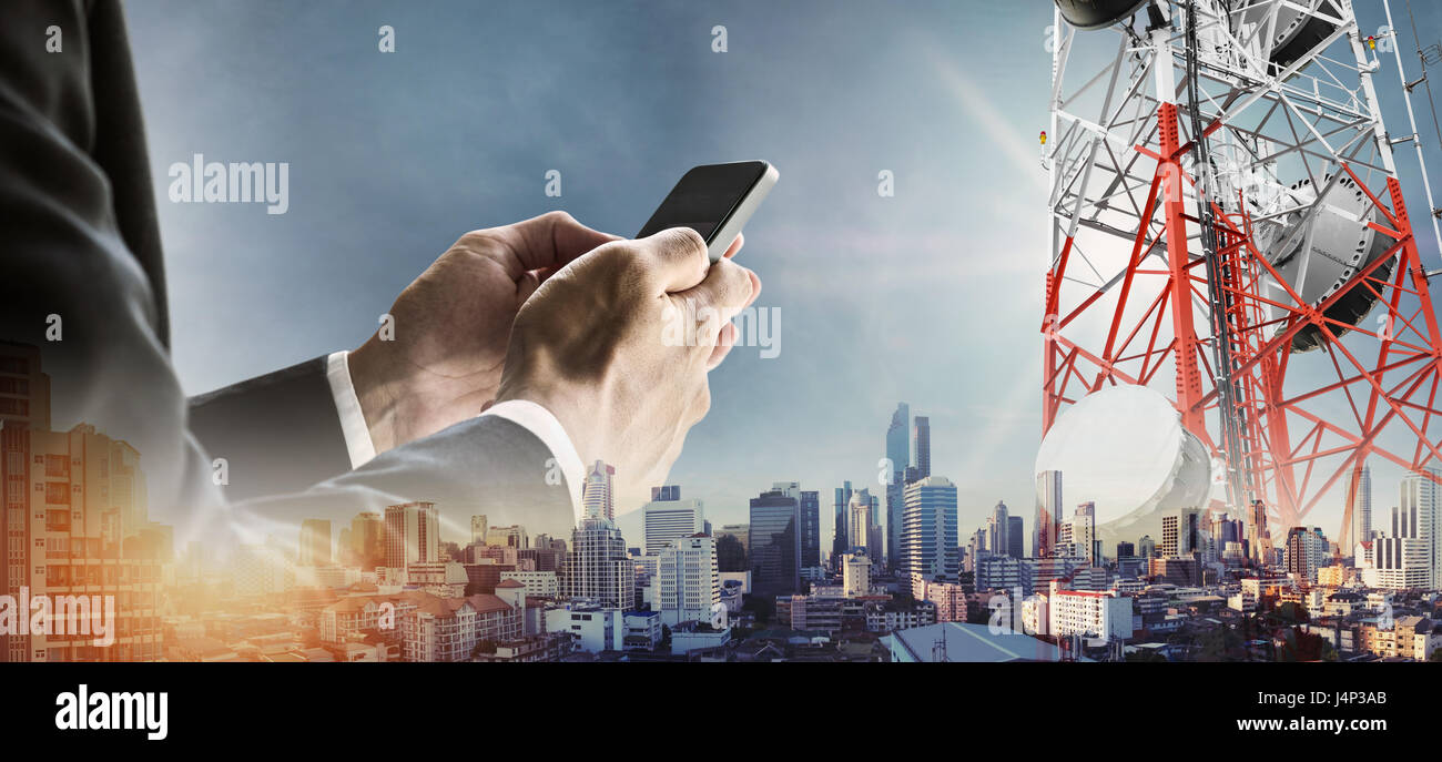Businessman using smartphone with double exposure modern cityscape in sunrise, and telecommunication towers - Stock Image