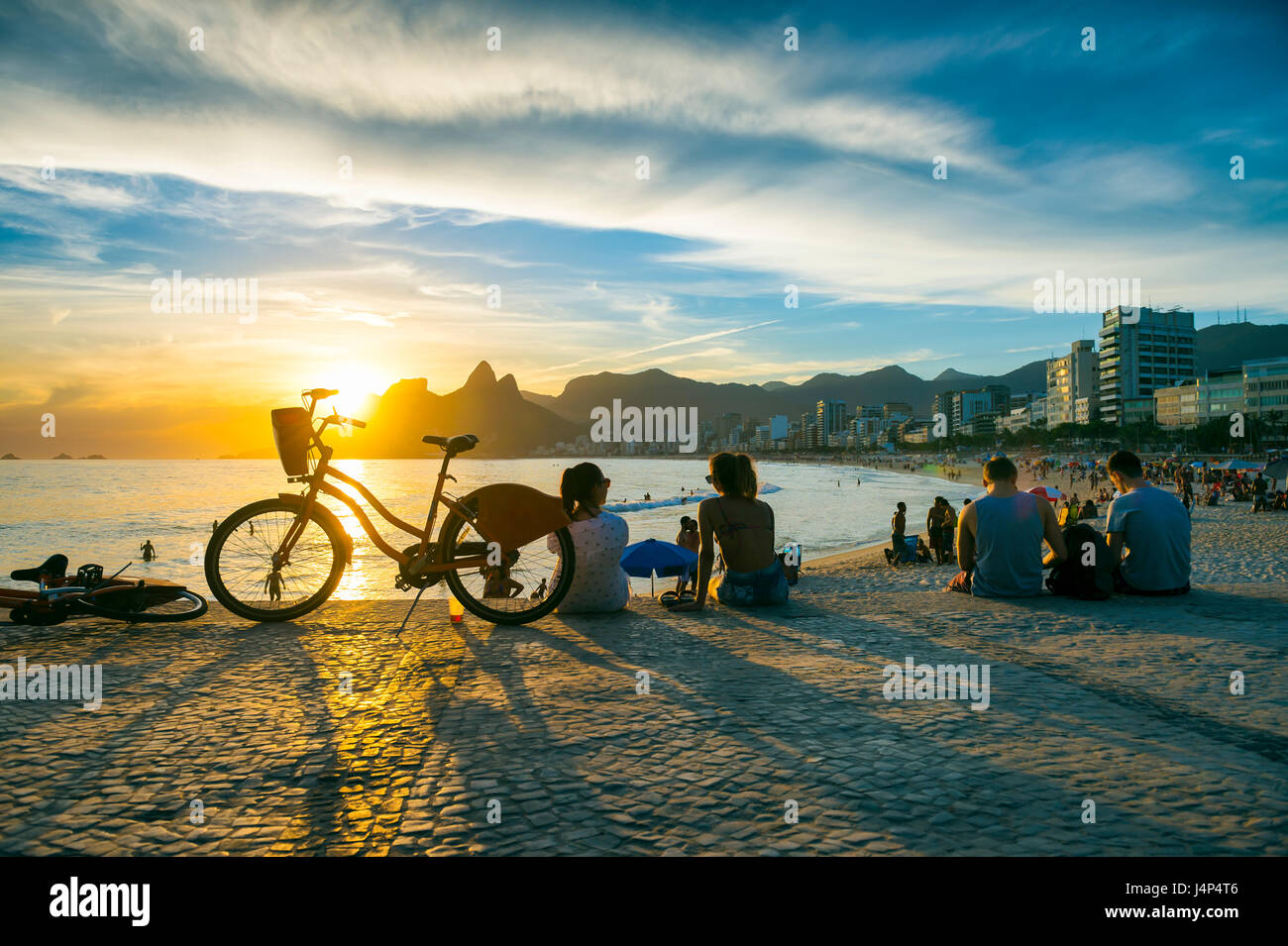 People sit watching the sunset at Arpoador, a popular summertime activity for locals and tourists, in Rio de Janeiro, - Stock Image