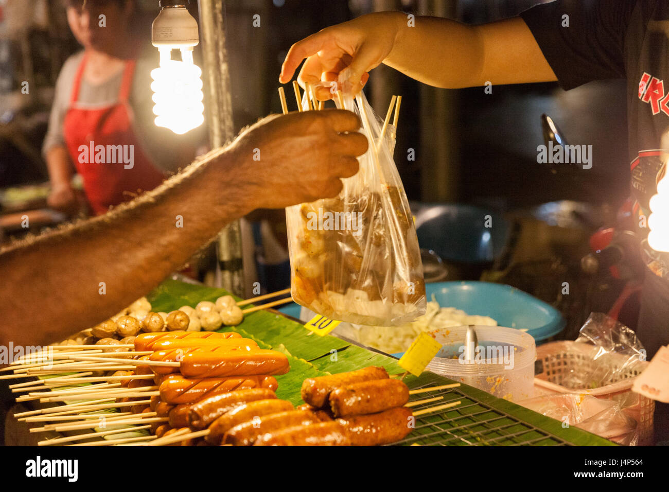 CHIANG MAI, THAILAND - AUGUST 21: Man buys meatballs at the Sunday Market (Walking Street) on August 21, 2016 in - Stock Image
