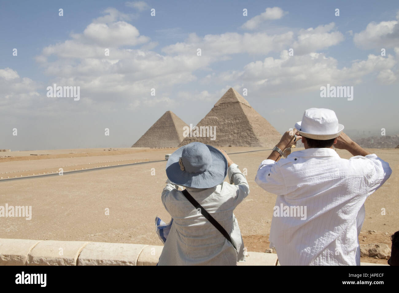Egypt, tourist couple, take photos, pyramids, Cairo, person, couple, tourist, back view, solar hats, sunscreen, - Stock Image