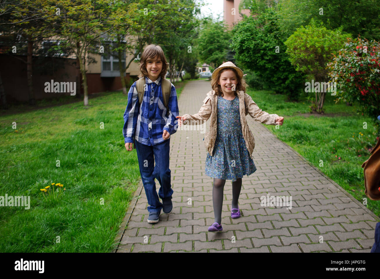 Elementary school students hurry to school. Schoolboy and schoolgirl with backpacks behind the back go to the lesson. - Stock Image