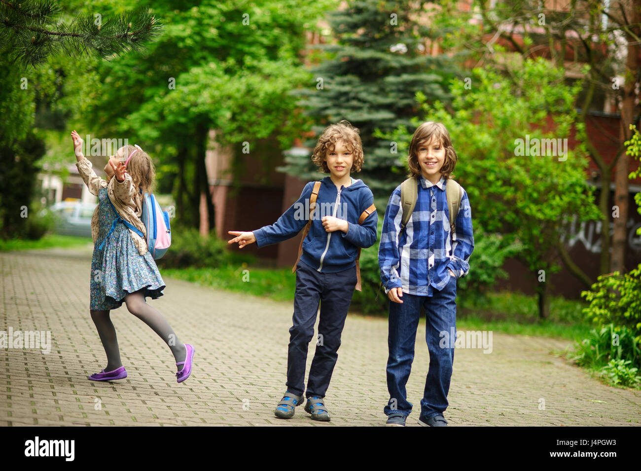 Three little friends hurry on lessons in school. The schoolgirl has noticed something on a tree. Boys smile. - Stock Image