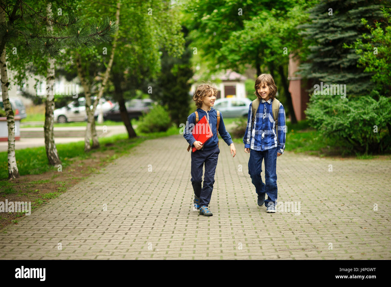 Elementary school students hurry to school. Schoolboys with backpacks behind the back go to the lesson. Friends - Stock Image