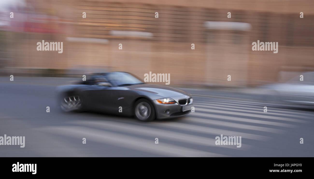 Roadster, BMW Z4, motion blur, scenery, town, zebra crossing, two-way traffic, no property release, - Stock Image