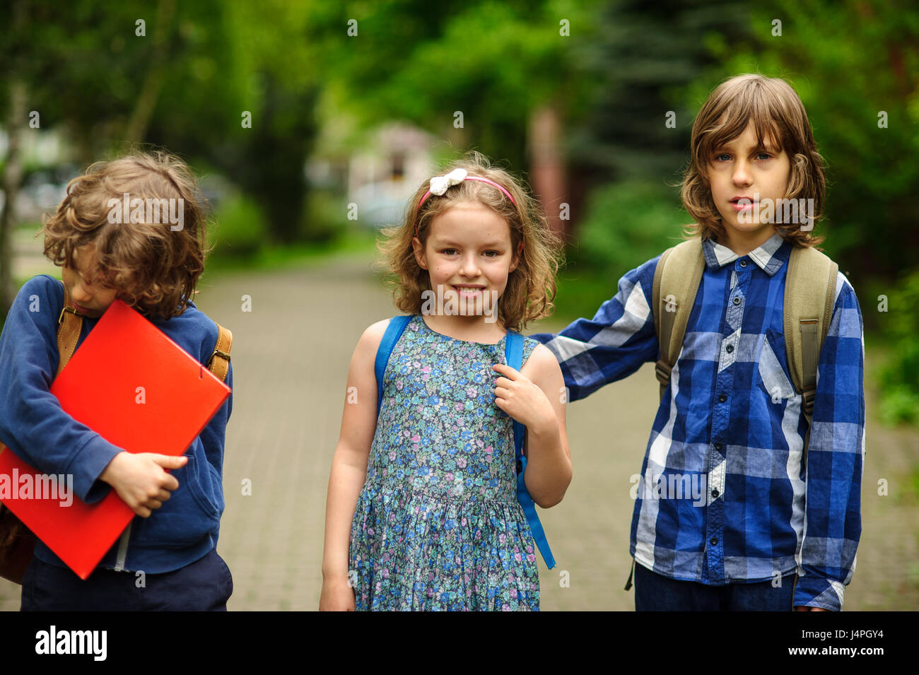 Little school students on the schoolyard. Three friends schoolmates. The girl and two boys with satchels behind Stock Photo