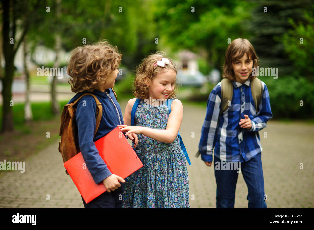 Little school students have started a game on the schoolyard. Two boys and the girl have fun waiting for the beginning - Stock Image