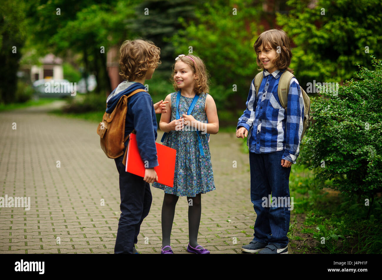 Little school students briskly and cheerfully talk on the schoolyard. Two boys and the girl have fun waiting for - Stock Image