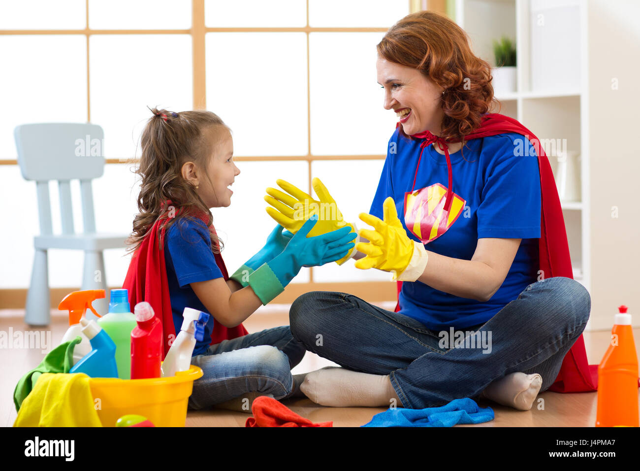 Happy mother with kid cleaning room and having fun playing at home. Family housework conception. - Stock Image