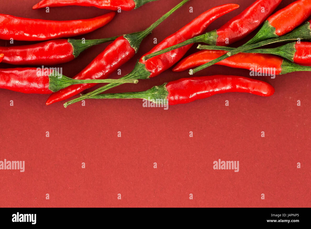 red hot chili peppers, popular spices concept - close-up on a beautiful handful of red hot pepper pods scattered - Stock Image