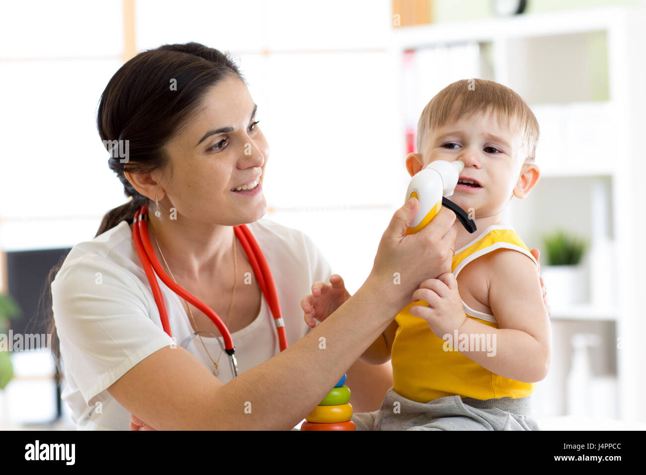 Female doctor pediatrician using nasal aspiration for child. Mucus suction patient kid baby. Stock Photo