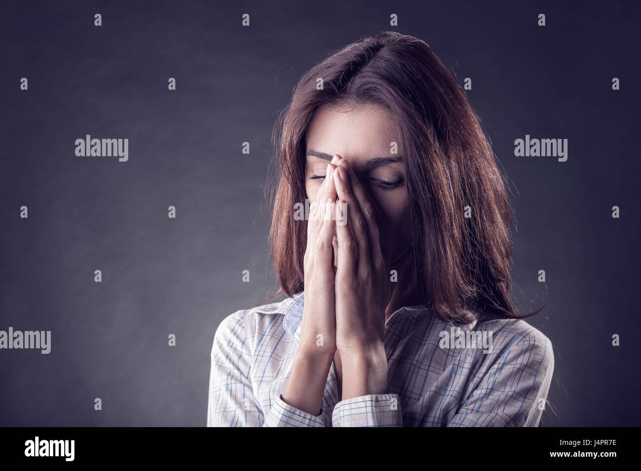 Young woman crying face in his hands on a black background - Stock Image