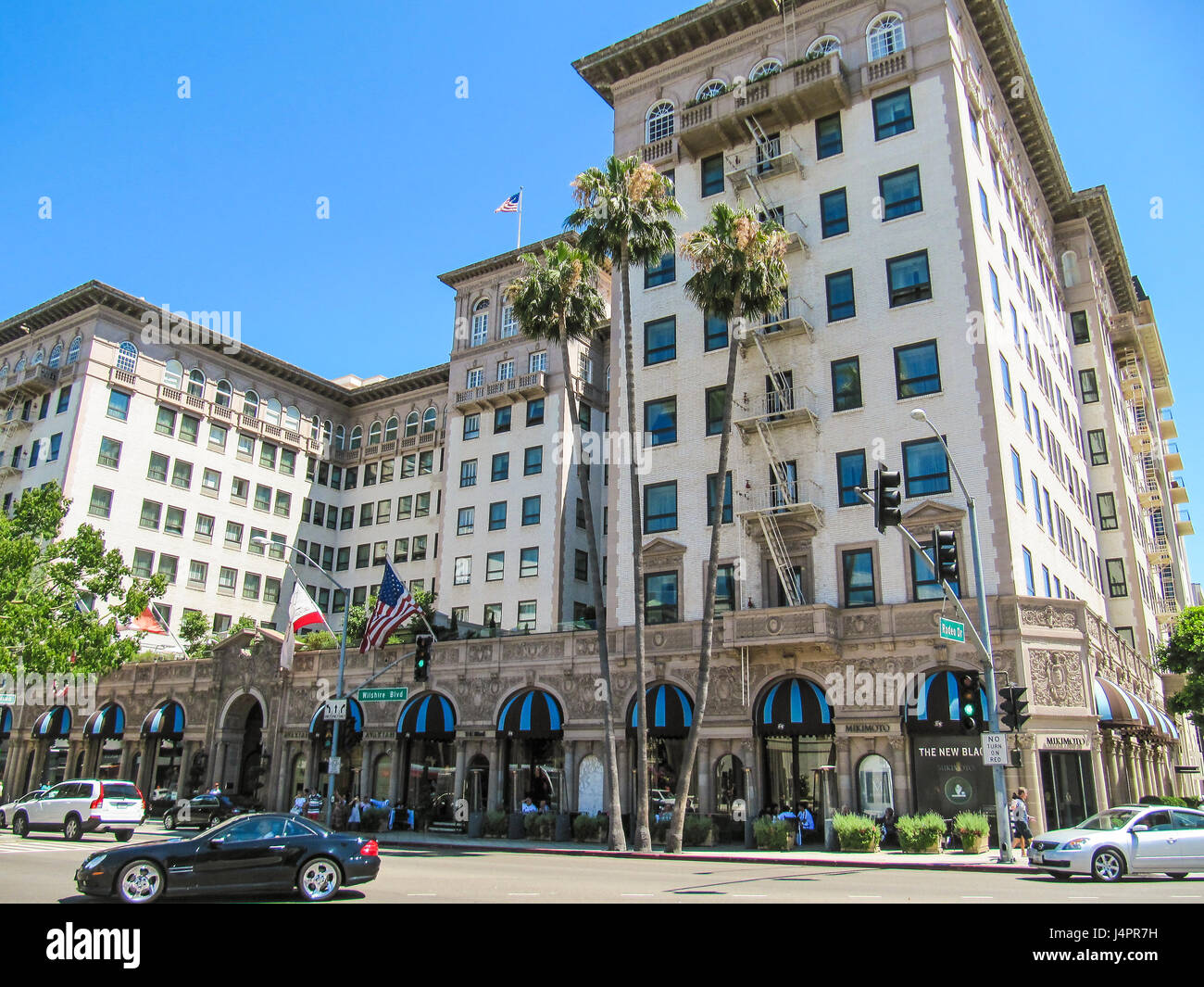 Los Angeles, USA - May 25, 2010: Wilshire boulevard with hotel, people, stores and street with cars - Stock Image