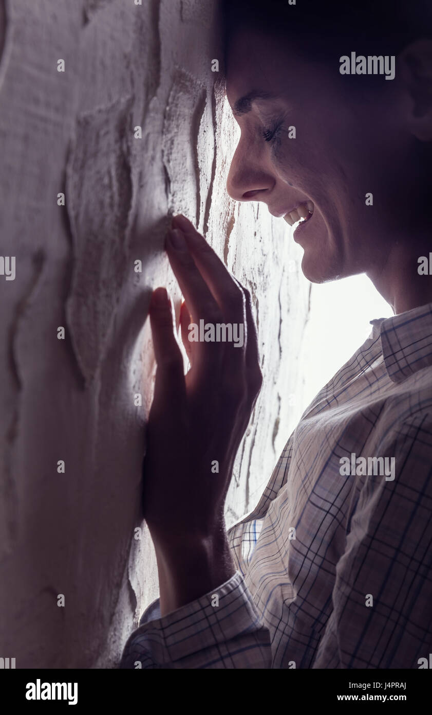 Young woman crying in wall - Stock Image