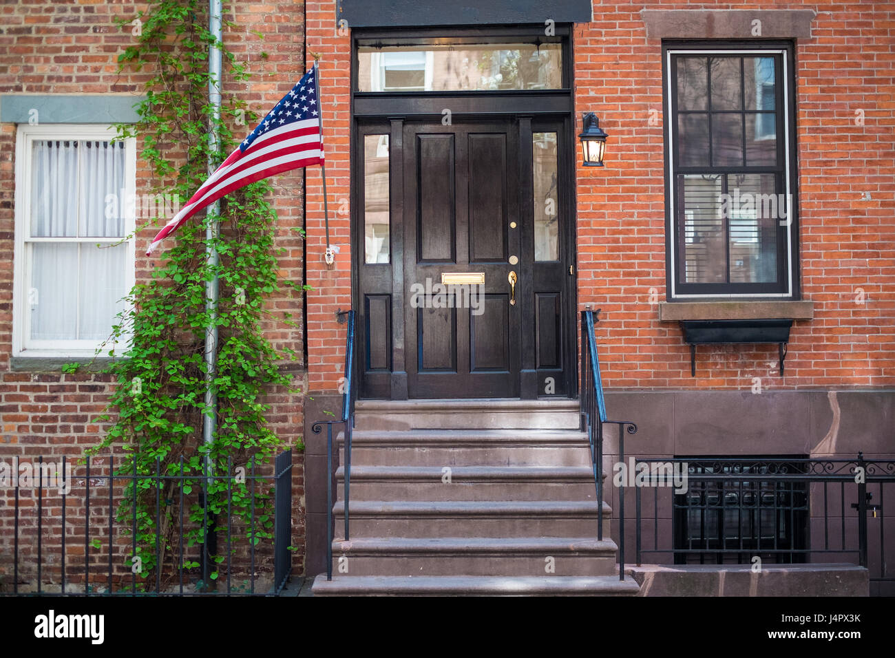 flag outside of entrance to red brick new york city apartment stock