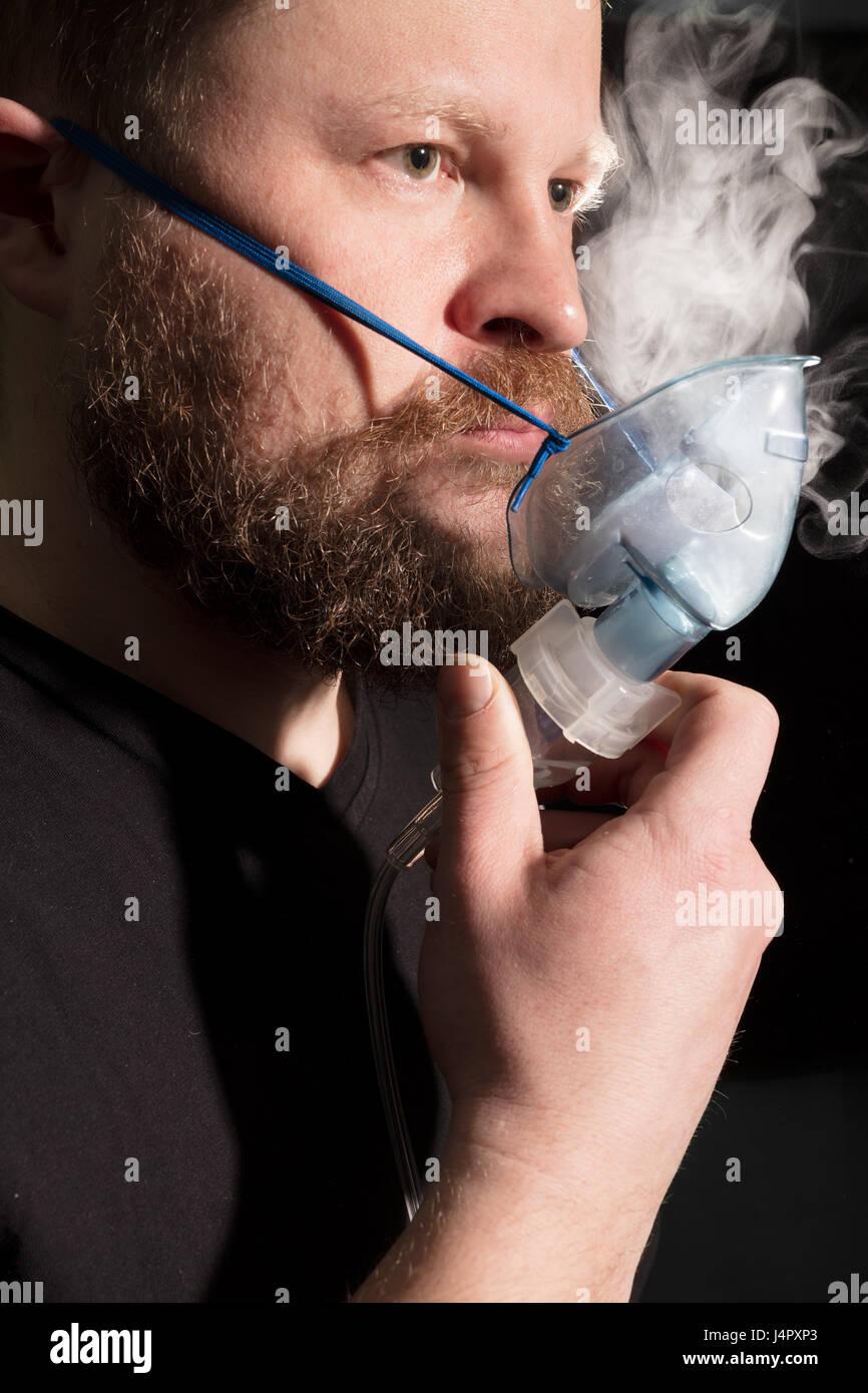 Man breathing through nebulizer mask on black background - Stock Image