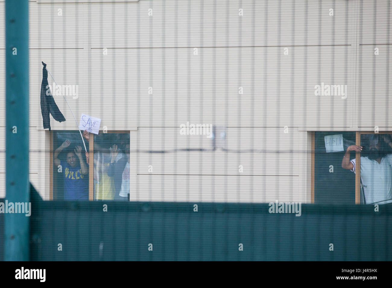 Milton Ernest, UK. 13th May, 2017. Detainees inside Yarl's Wood Immigration Removal Centre hold up signs in - Stock Image