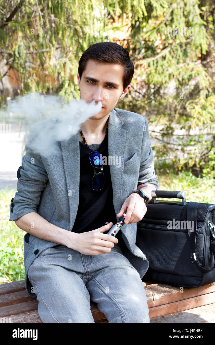 Thoughtful young businessman smokes a vape in a park in the spring afternoon - Stock Image