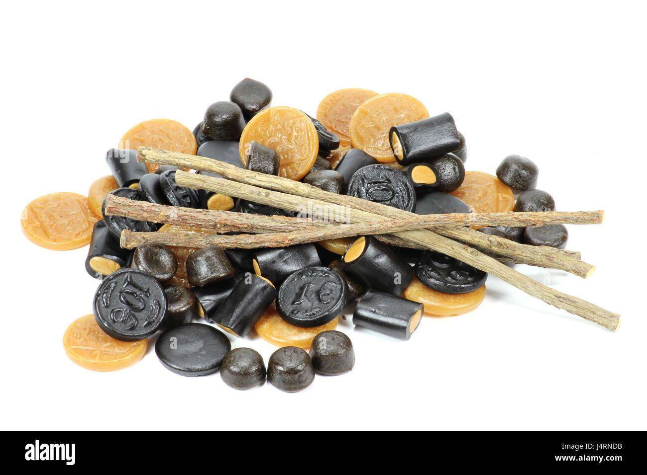 licorice candies with dried sticks of licorice root isolated on white background - Stock Image
