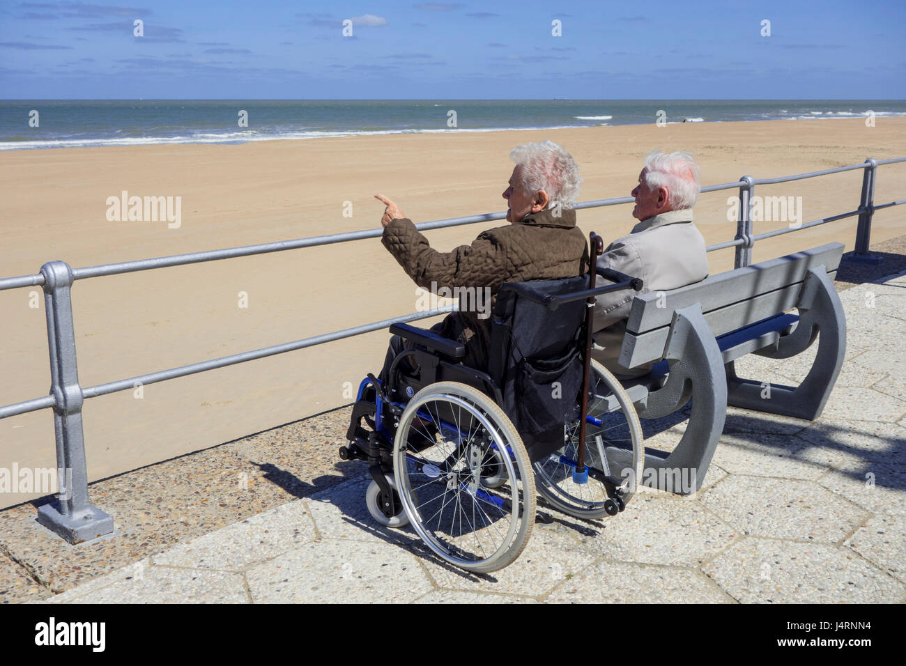 Disabled elderly woman in wheelchair and retired husband sitting on a bench at promenade along the coast on a cold Stock Photo