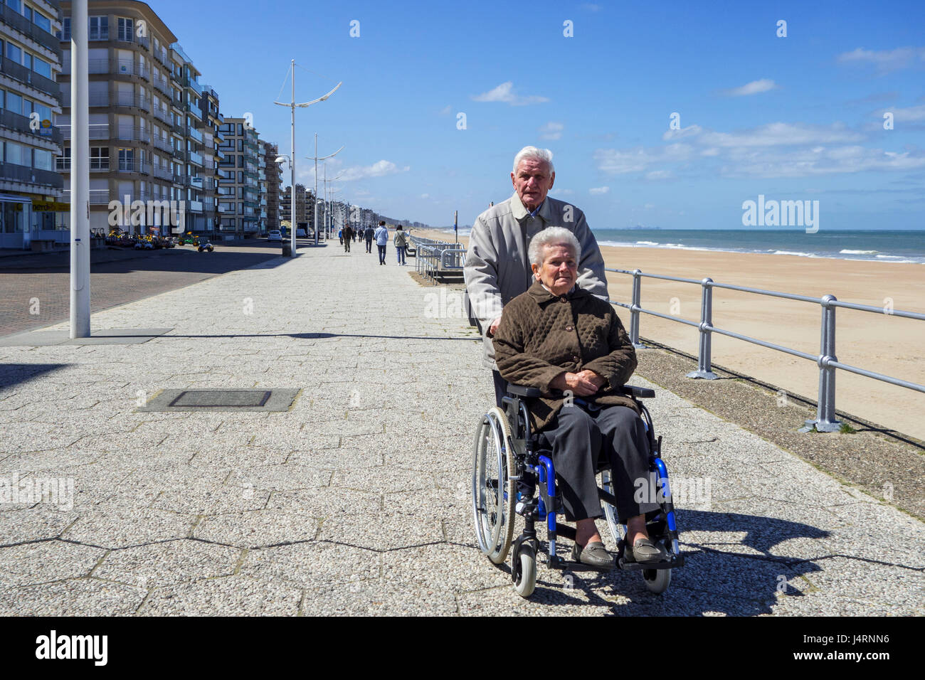 Retired husband taking disabled elderly wife in wheelchair for a walk on promenade along the Belgian North Sea coast - Stock Image