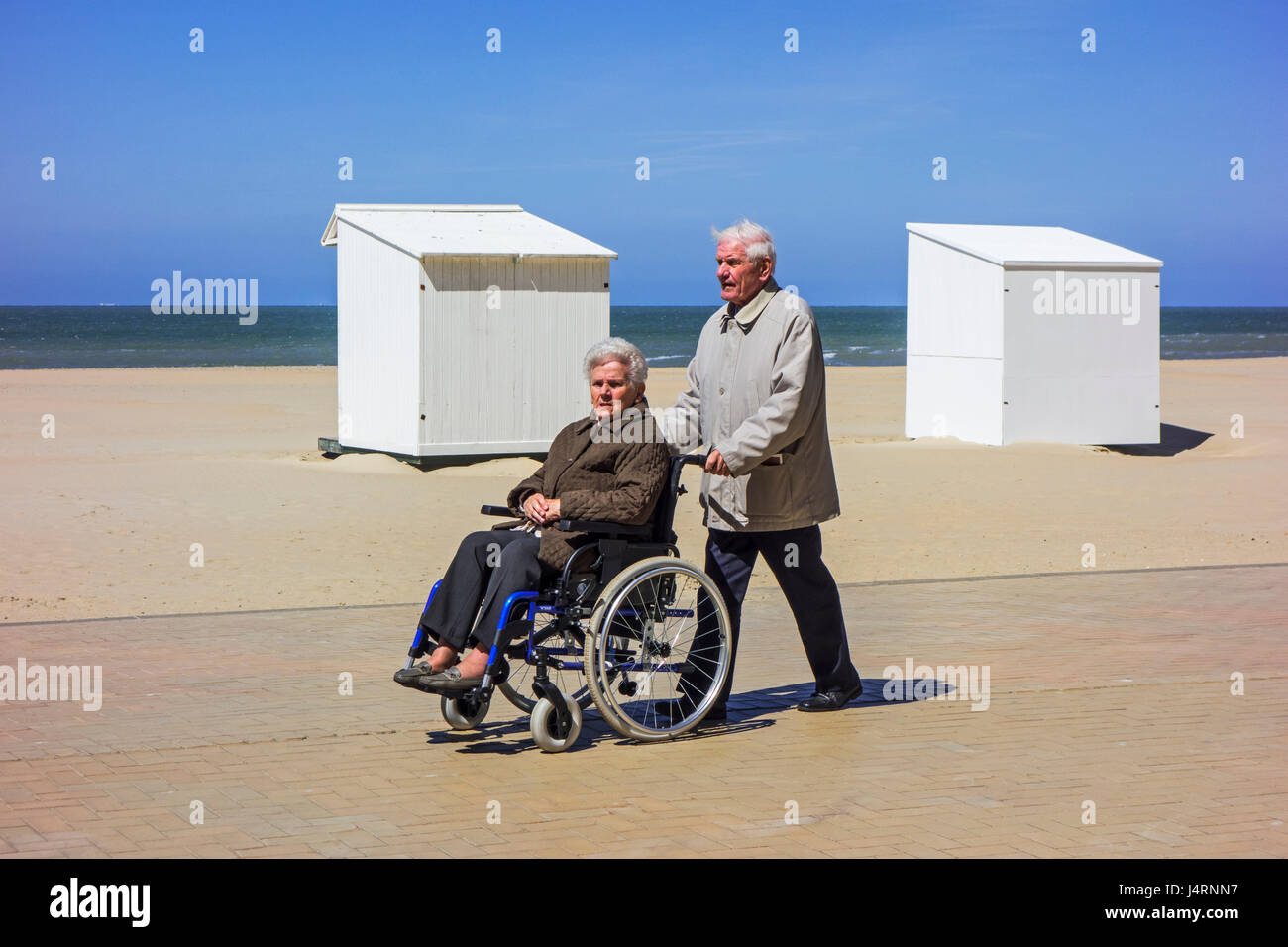 Retired husband taking disabled elderly wife in wheelchair for a walk on promenade along the coast on a cold sunny - Stock Image