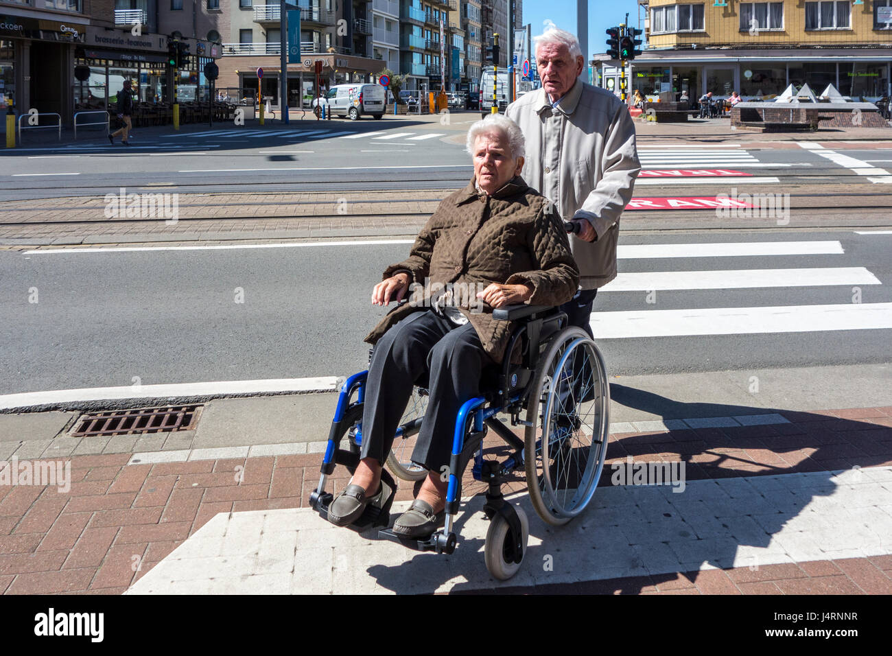 Retired husband with disabled elderly wife in wheelchair traversing street over pedestrian crossing / crosswalk - Stock Image