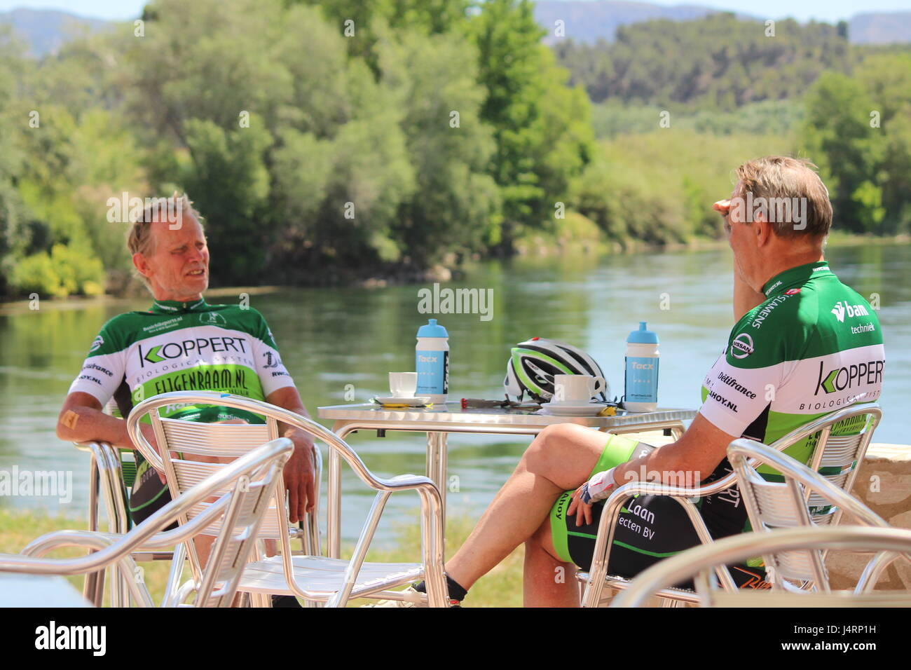 Two male cyclists taking a coffee break beside the river Ebro in Miravet in  Spain, wearing green and white Lycra - Stock Image