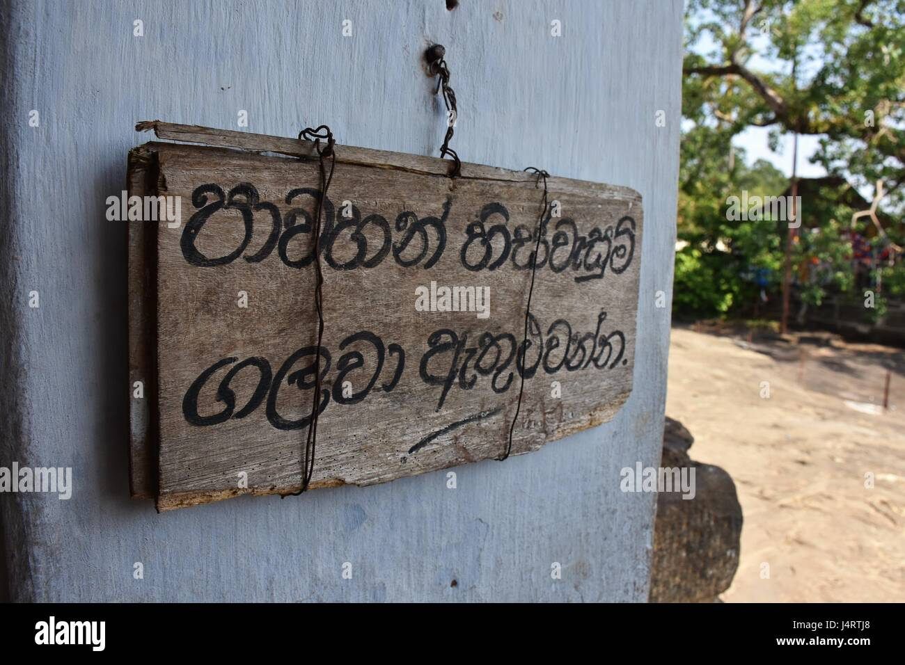 """A hand written notice, on a wooden plank at the entrance to the Gadaldeniya Temple reads,""""Please remove your shoes Stock Photo"""