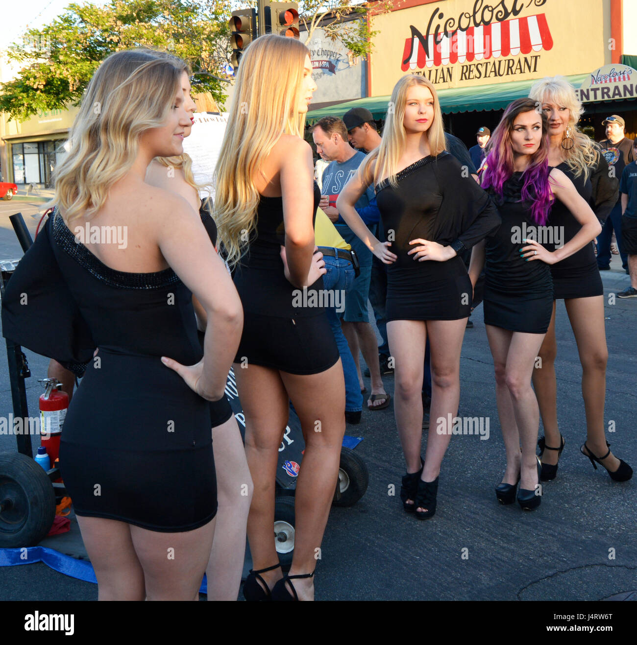 Blond girl models in short black dresses with motorcycles on Main Street, in small town USA - Stock Image