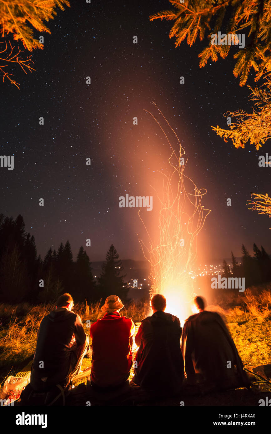 Four friends sitting near campfire in high mountains. Amazing night scene. Man friendship concept Stock Photo