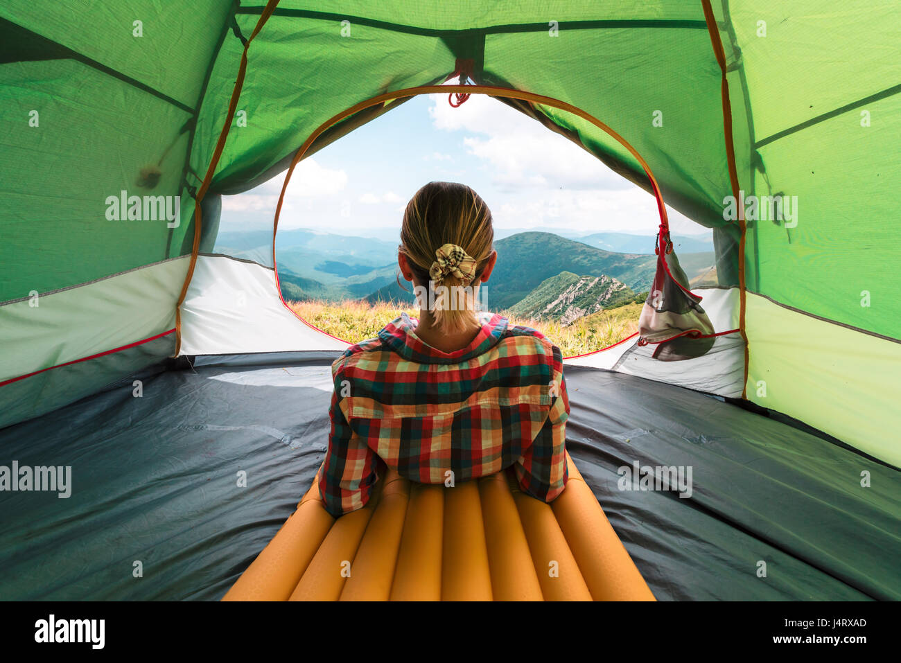 Girl sitting in they tent against the backdrop of an incredible mountain landscape. Sunny day in highland - Stock Image