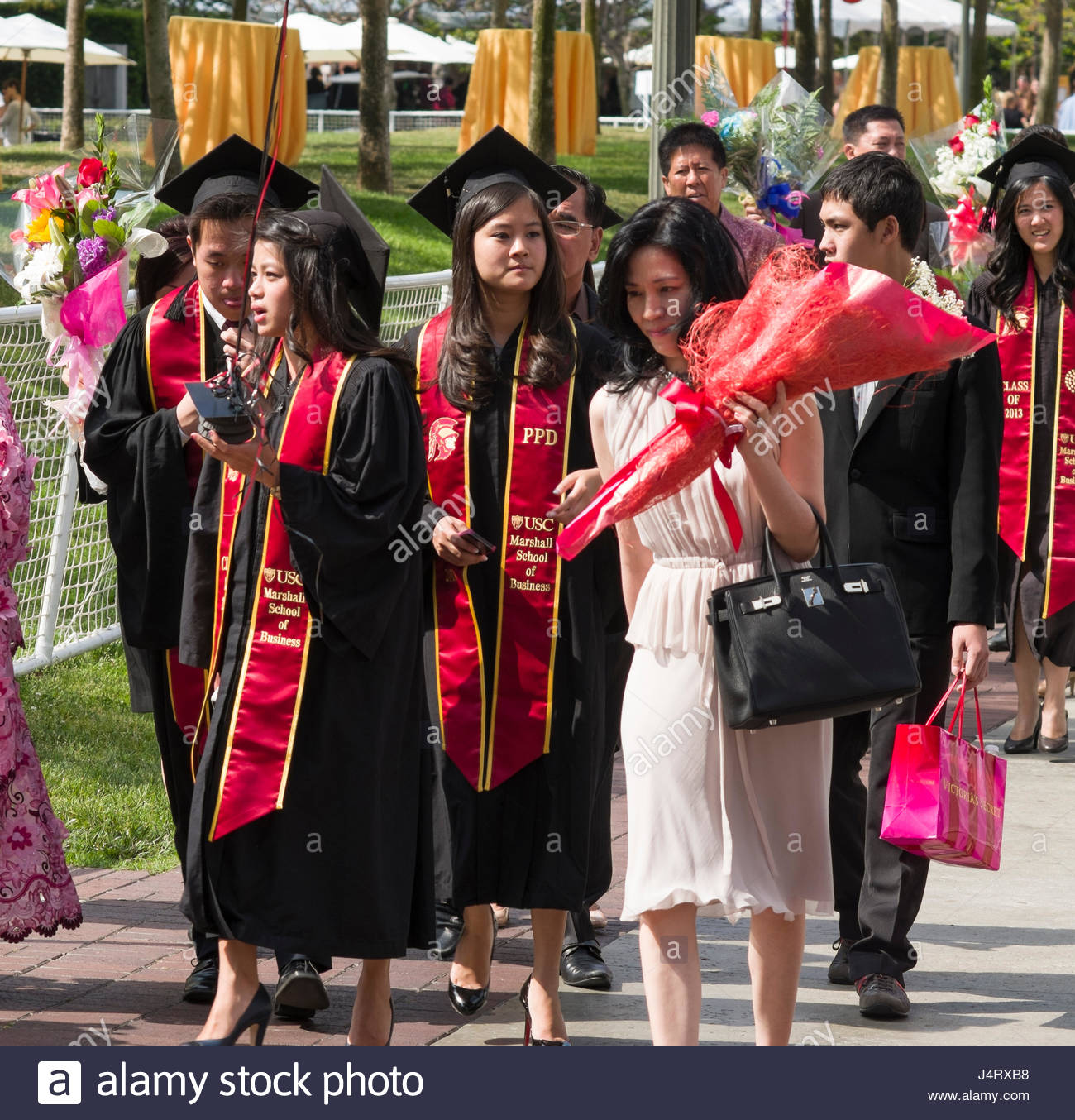 Graduates in cap and gown with family and friends walking on campus ...