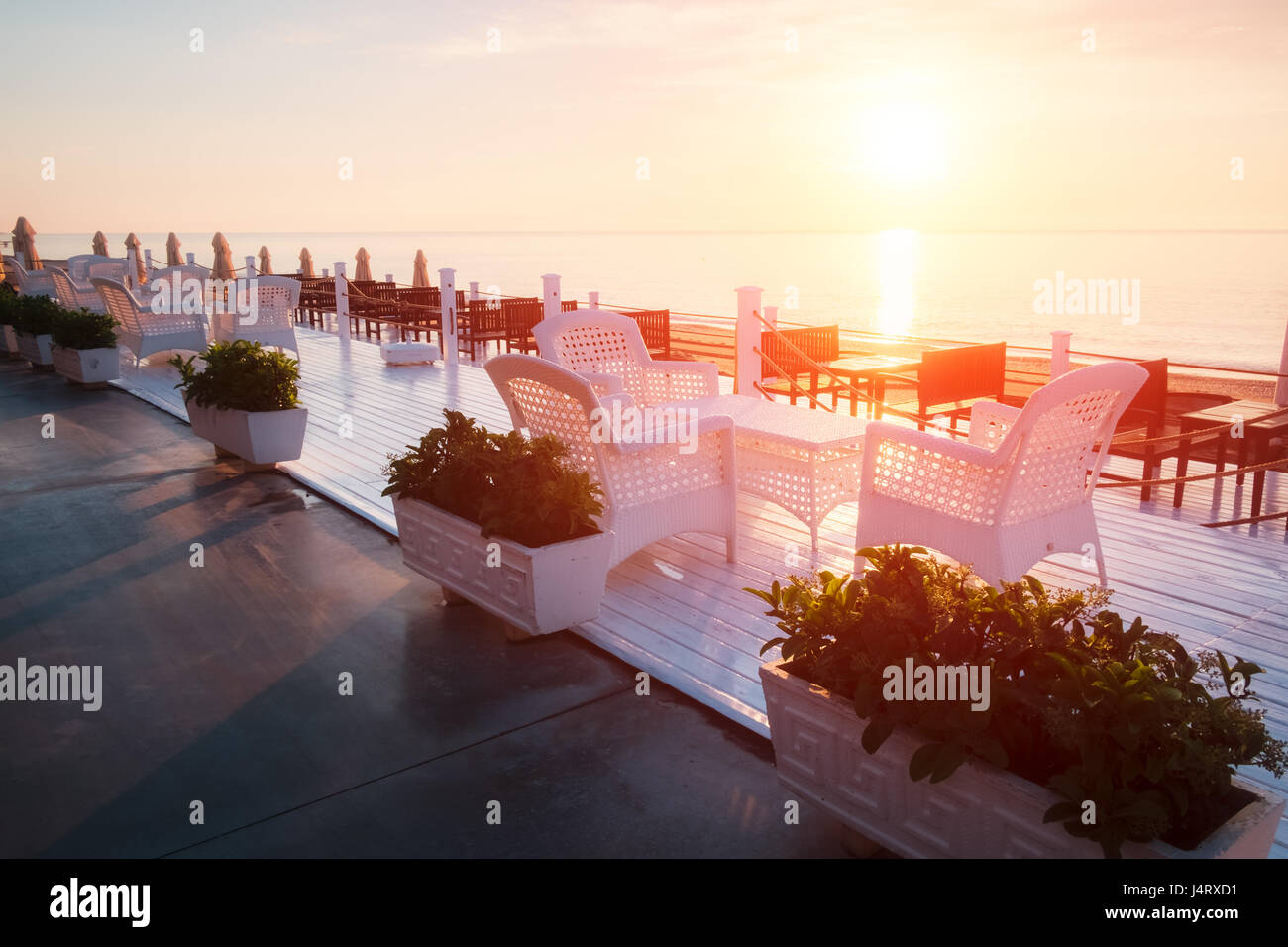 Summer restaurant on beach. Breathtaking view on mediterranean sea. White wooden terrace and braided furniture - Stock Image
