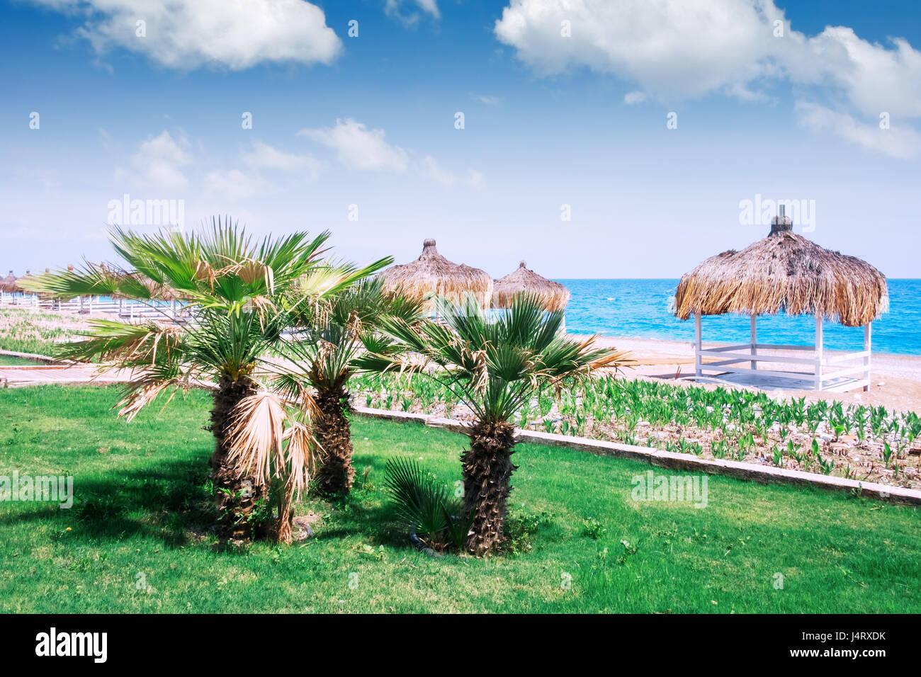 Summer arbors on beach. Breathtaking view on mediterranean sea. White wooden summerhouses on sunny day. Blue sky - Stock Image