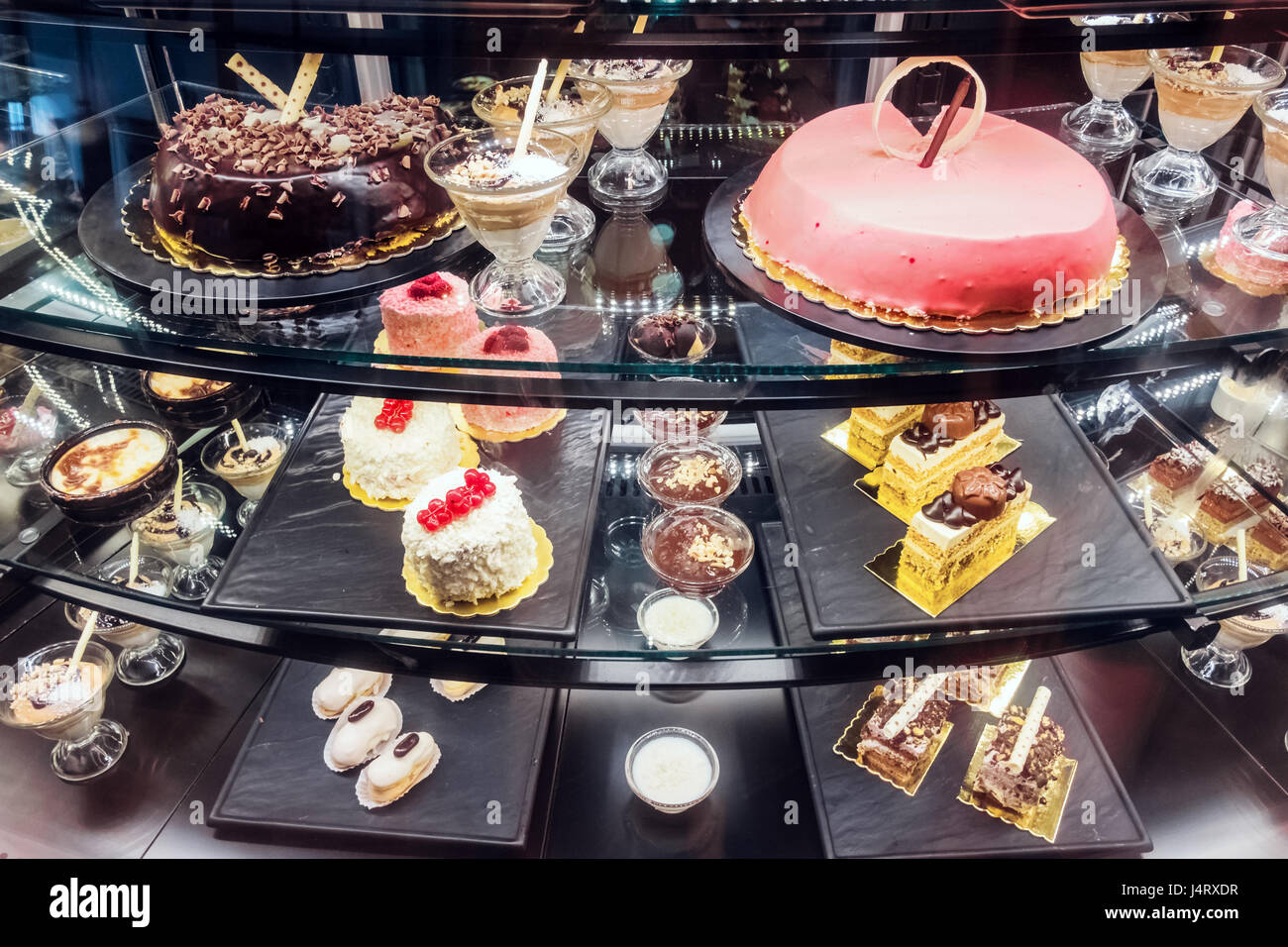 Different desserts on bakery shop-window. Sweets and cakes for every taste - Stock Image