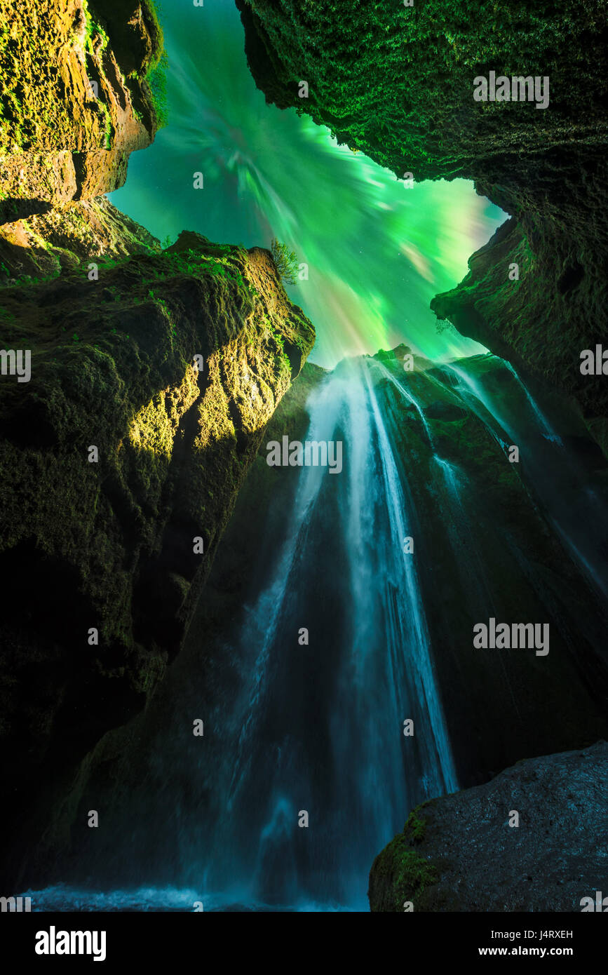 Green aurora light behind unique Gljufrabui waterfall in cave. Iceland, Europe. Courtesy of NASA. Photo collage Stock Photo