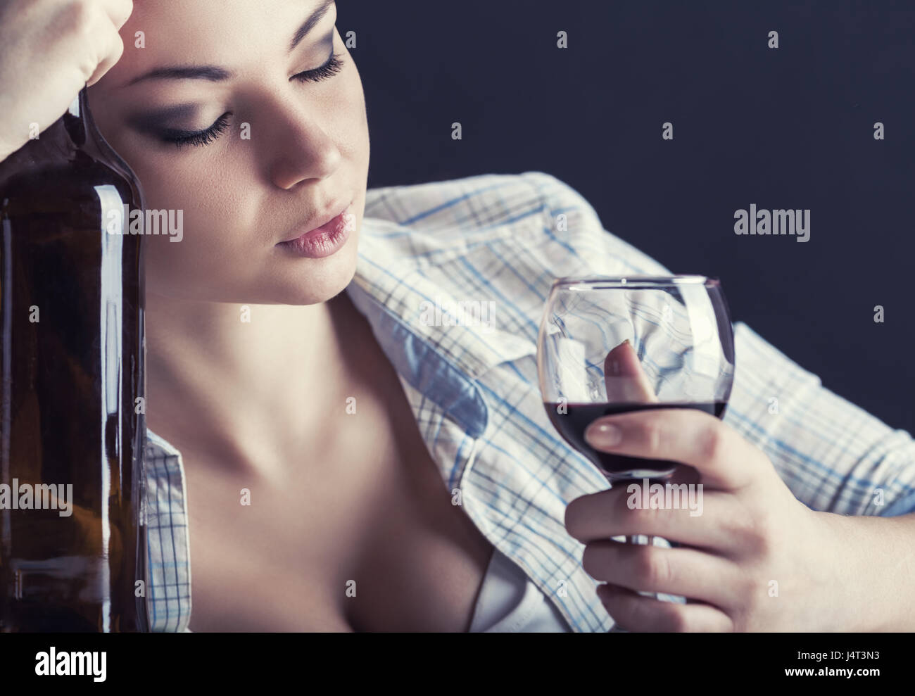 Young beautiful woman in depression, drinking alcohol - Stock Image
