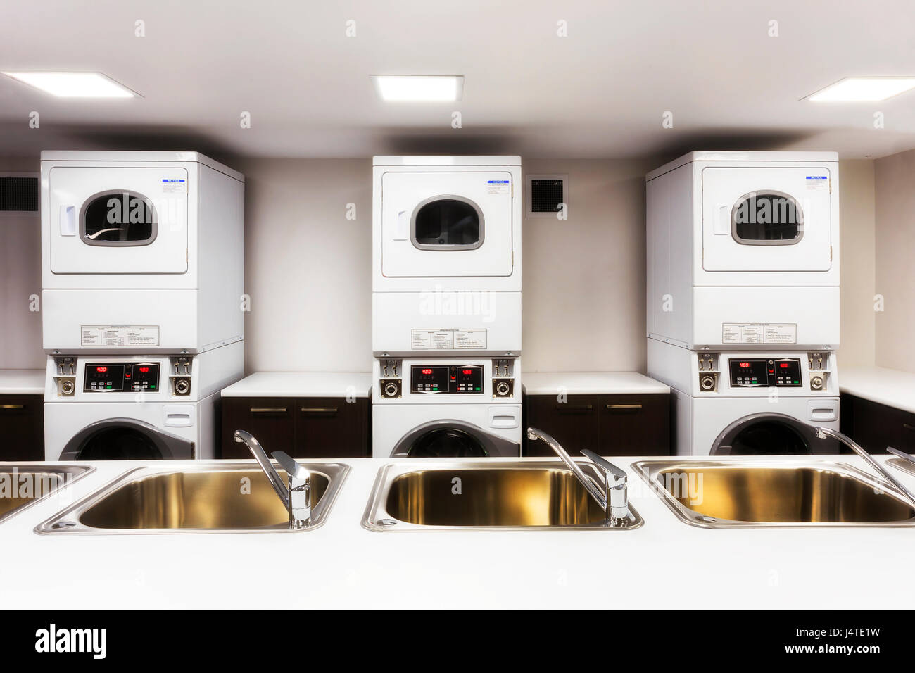 Big laundromat with washing and drying machines behind sinks with taps ready for customers with laundry. - Stock Image