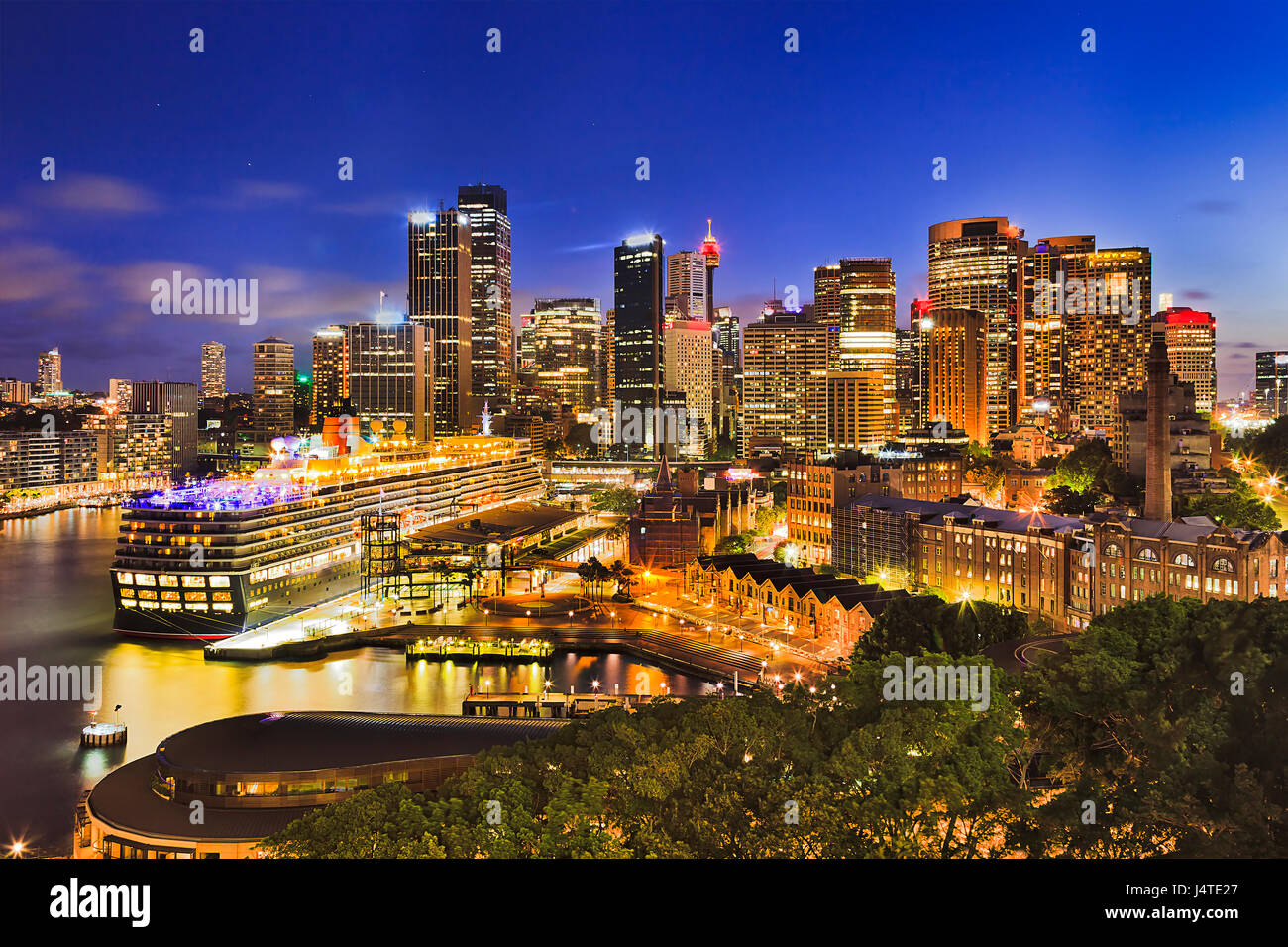 Sydney harbour around Circular quan and the Rocks brightly illuminated at sunset. Popular tourism destination from - Stock Image