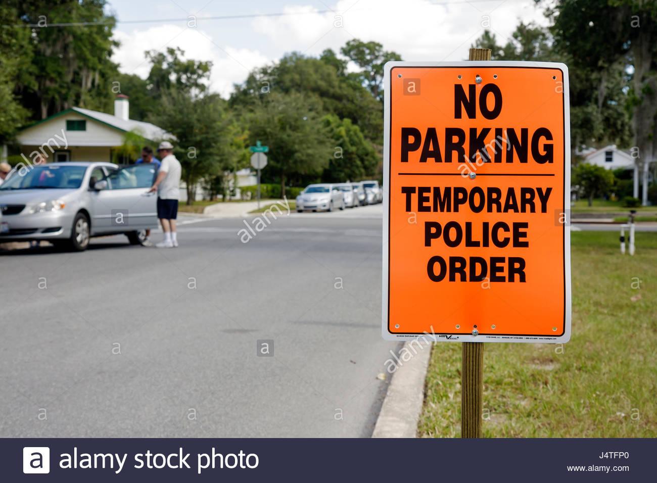 Mount Dora Florida Mt. Annual Craft Fair temporary sign police order warning no parking street parked car man - Stock Image