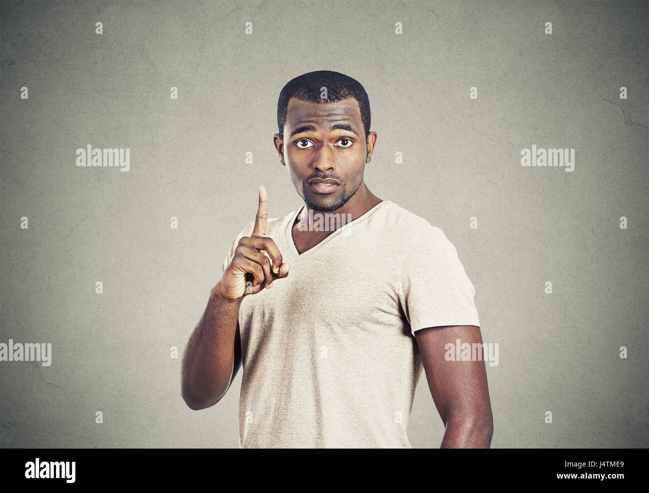 Closeup portrait young man pointing up having idea, solution, showing with index finger number one isolated grey - Stock Image