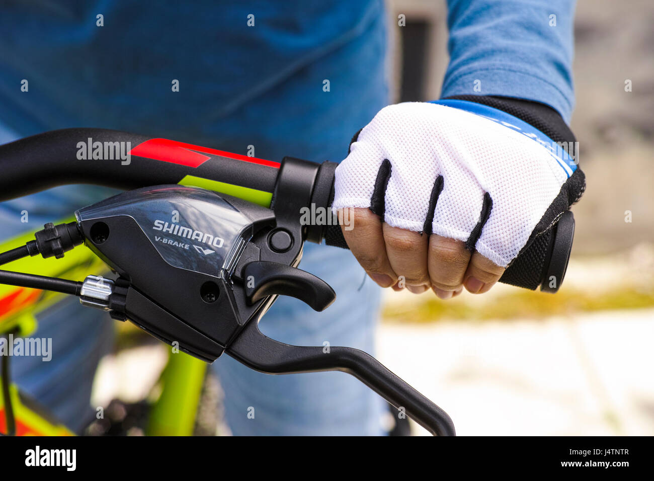 Tambov, Russian Federation - May 07, 2017 Child hand with glove on handlebars with Shimano speed shift and brake - Stock Image