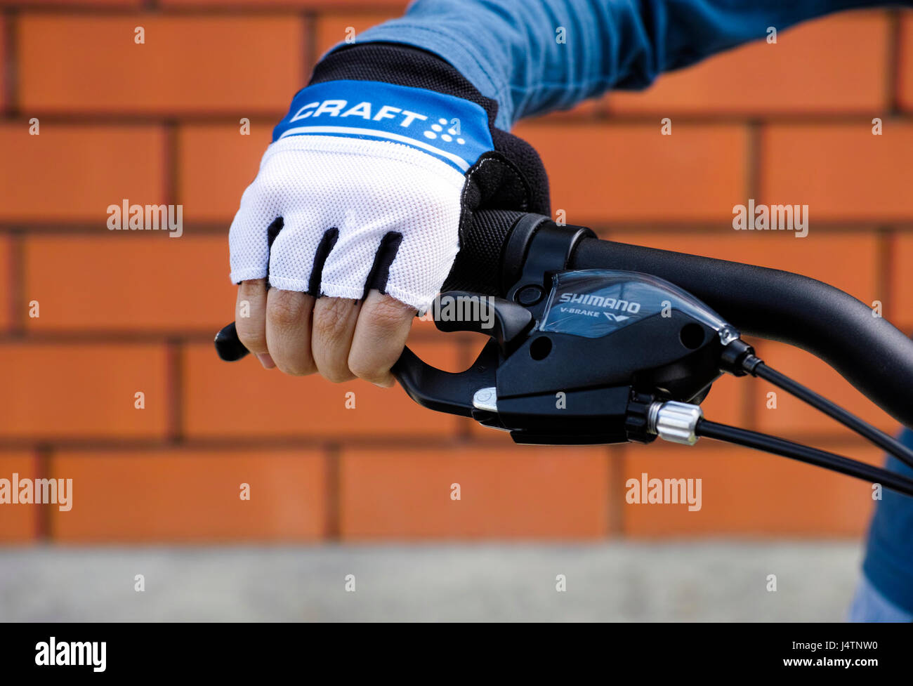 Tambov, Russian Federation - May 07, 2017 Child hand with Craft glove on handlebars with Shimano brake lever. - Stock Image
