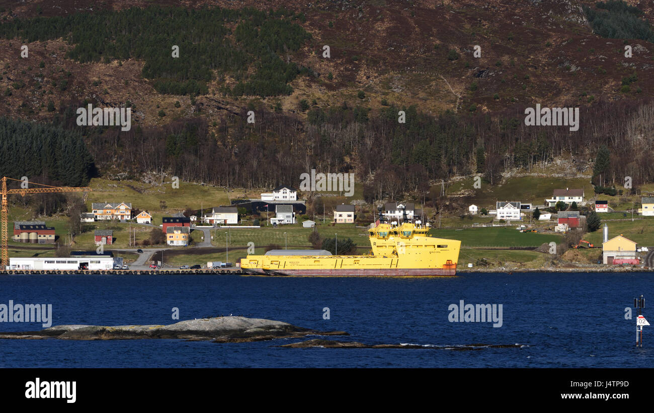 The yellow painted off shore supply ship World Opal moored in Torvik on the island Leinøya. Torvik, Møre - Stock Image
