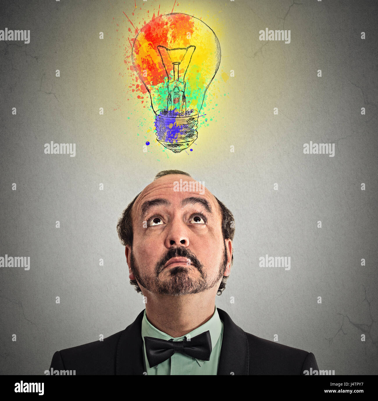 Concept of Creative business idea with colorful lightbulb. Portrait middle aged businessman came up with solution - Stock Image