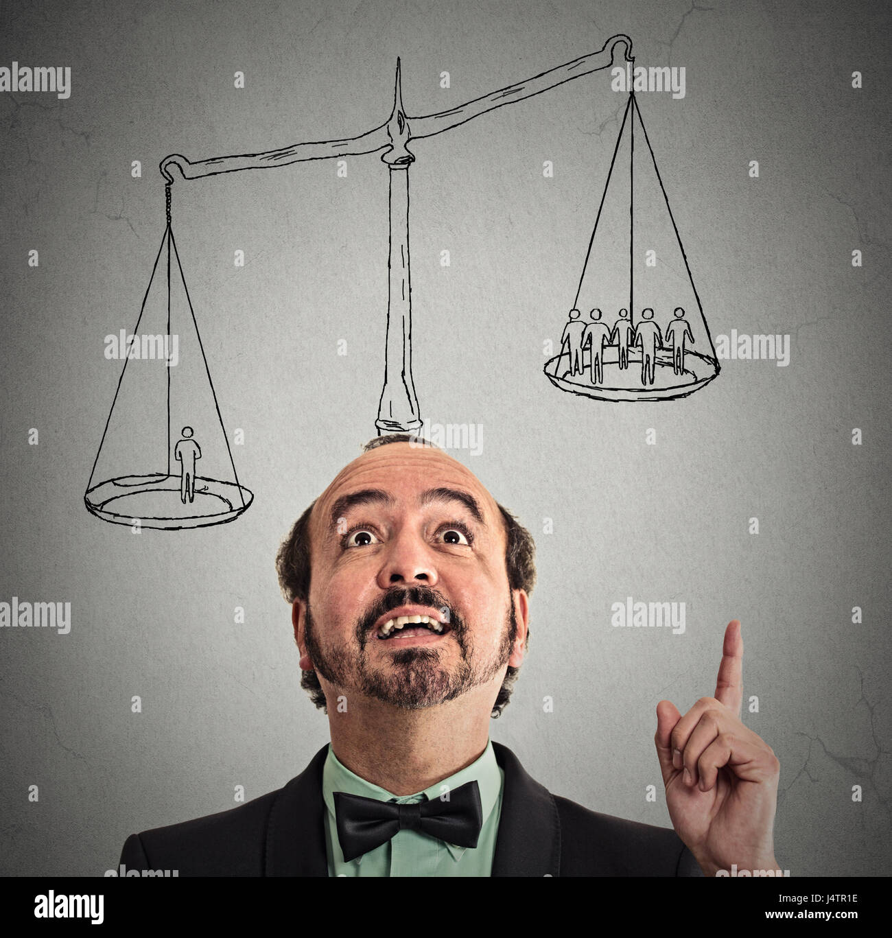 businessman with scale above head has idea solution one man weighting more than group off business people on balance. - Stock Image