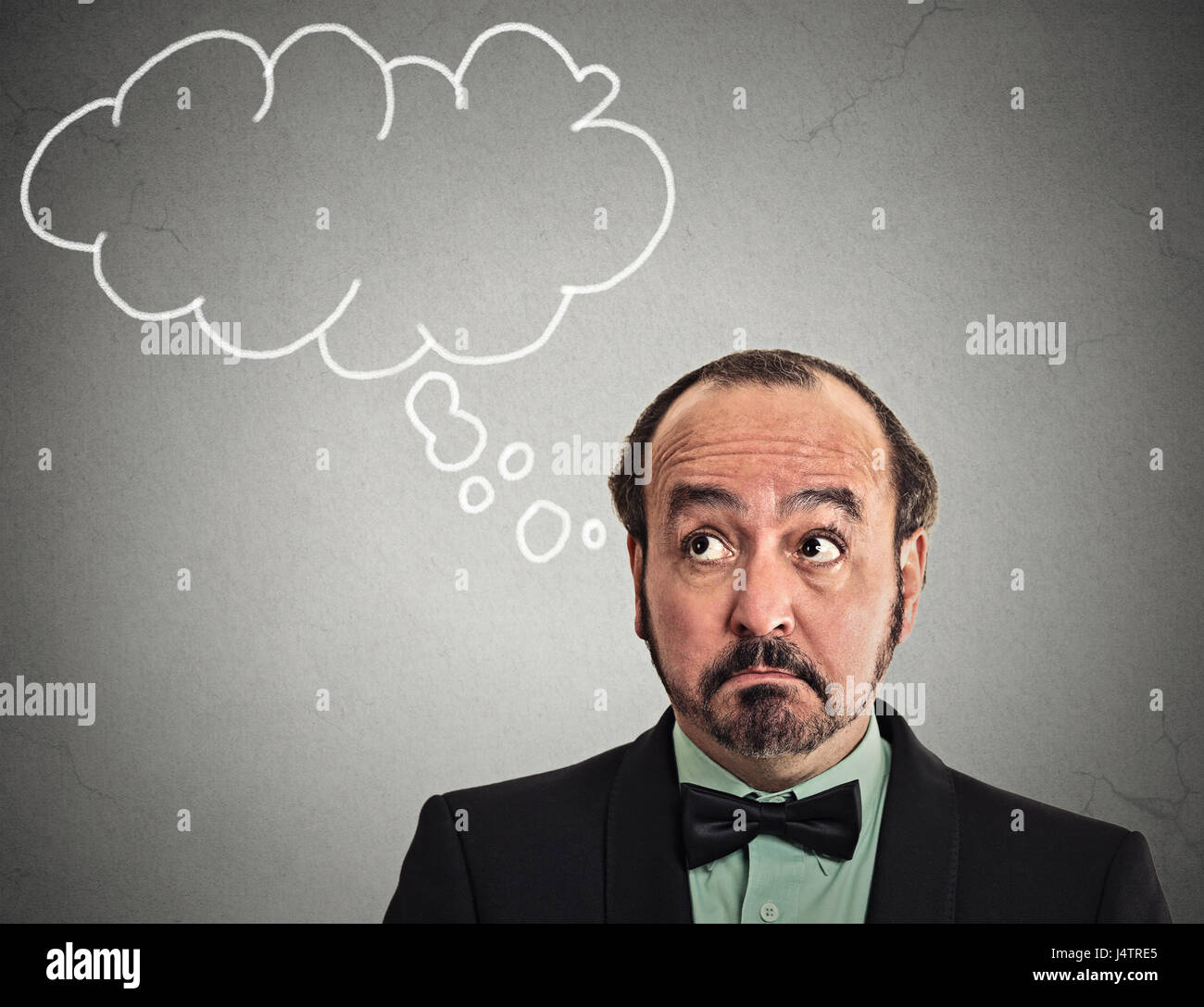 Headshot middle aged man with thoughtful puzzled face expression blank bubble with copy space above head looking - Stock Image
