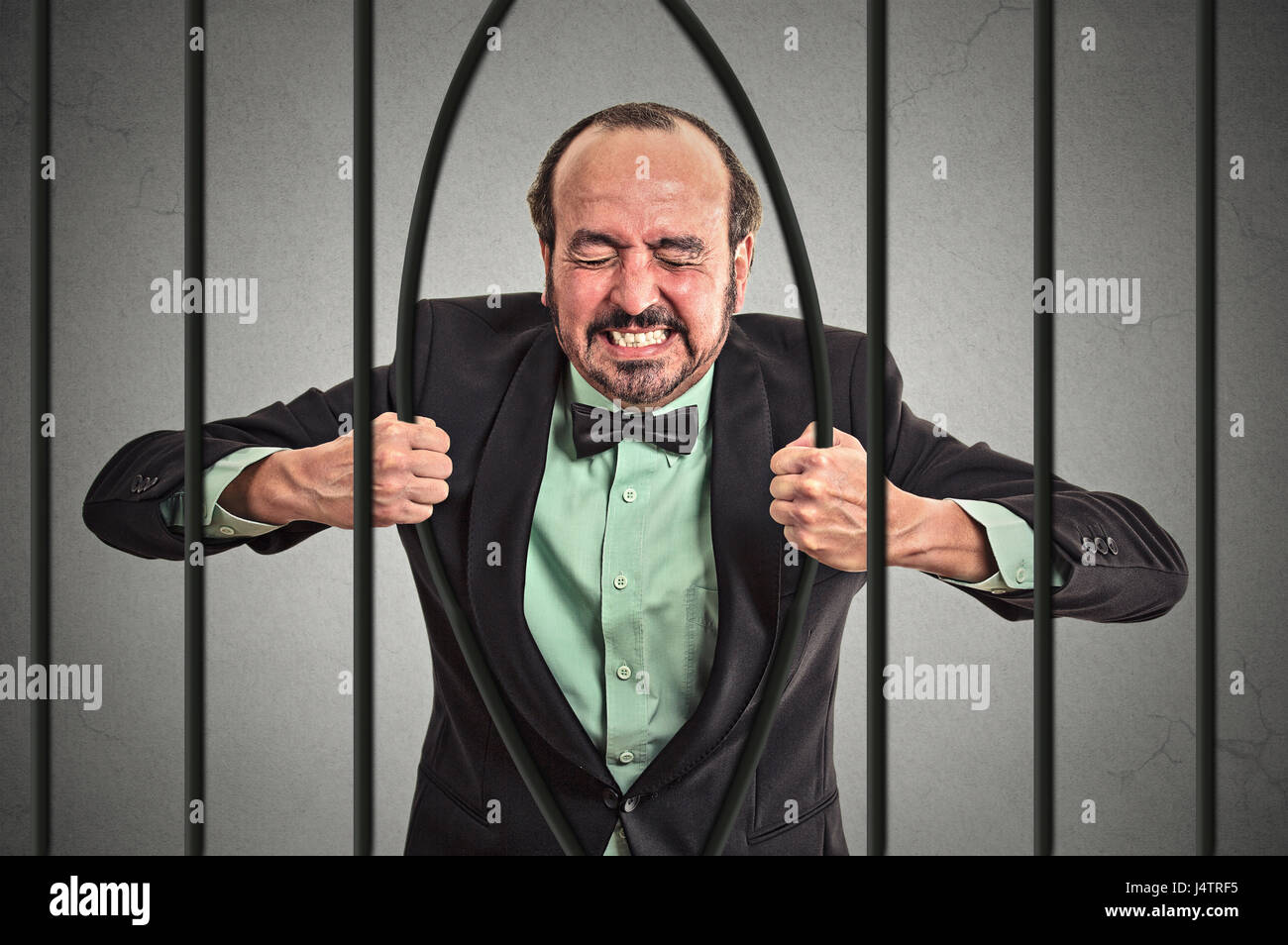 Furious strong middle aged businessman bending bars of his prison cell grey wall background. Life limitations, law - Stock Image